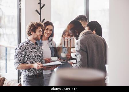 Business di successo di persone stanno usando i gadget, parlando e sorridente durante la pausa caffè in ufficio Foto Stock