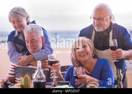 Seniors caucasica adulto soggiorno insieme all'aperto facendo il pranzo in terrazza. vacanza e concetto di amicizia con sorrisi e il vino e il tempo del partito