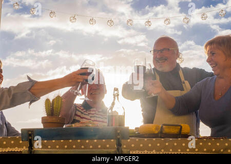 Uomini e donne adulti cheers con vino all'aperto nel patio terrazza tetto per festeggiare in vacanza o compleanno o evento. anziani lifestyle giorno felice vita c Foto Stock
