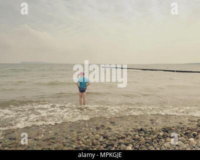 Ragazzo in blu nero abbigliamento sportivo soggiorno a freddo mare schiumoso. Capelli biondi kid in onde alla spiaggia sassosa. Giornata di vento, nuvoloso cielo blu su seascape Foto Stock