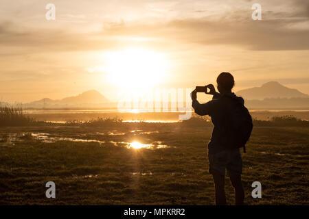 Silhouette di donna tenendo uno smartphone per scattare foto al di fuori durante l'alba o al tramonto. Foto Stock