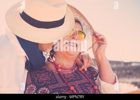 Adulti soggiorno insieme con il bacio e abbraccio sotto il sole con cappelli e occhiali da sole e collana. Il vero amore per sempre insieme concetto Foto Stock
