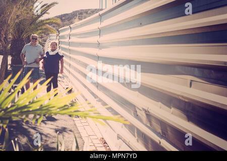 Due anziani a camminare per strada con pugs nascosti i cani in estate sotto il sole Foto Stock