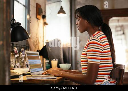 Giovane donna seduta alla scrivania in un loft lavorando sul computer portatile