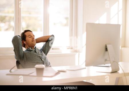 Imprenditore in un momento di relax a casa seduti davanti al suo tavolo di lavoro. L'uomo prendendo una pausa e ascoltare la musica con gli occhi chiusi. Foto Stock