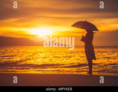 Silhouette solitaria e premuto donna con ombrello e di stare di fronte al mare. Foto Stock