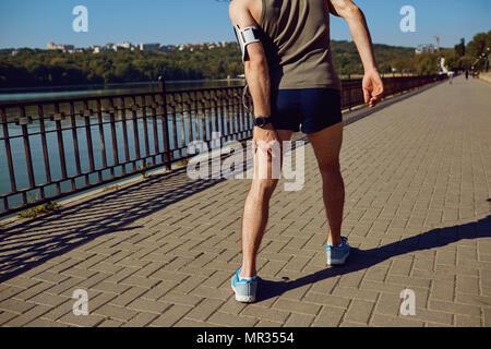 Pregiudizio, stretching, livido su una corsa in un runner Foto Stock