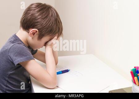 Stanco bambino facendo i compiti a casa. Il ragazzo stufi e si copre il viso con le mani. Istruzione, scuola, difficoltà di apprendimento concetto Foto Stock