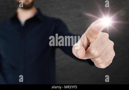 Uomo in camicia blu toccando interfaccia traslucido con un dito di una mano modello Foto Stock