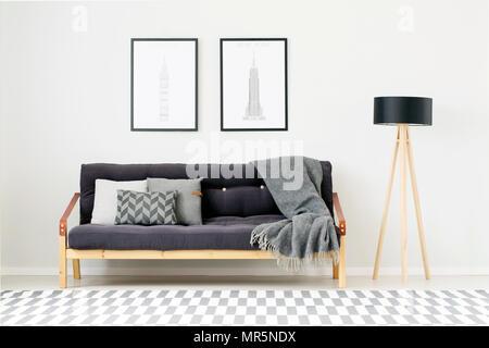 Divano Nero Cuscini : Lampada nera e il poster accanto al divano con cuscini grigi