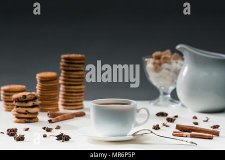 Tazza di caffè nero sulla tabella con i cookie e spezie Foto Stock