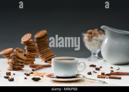 Tazza di caffè versato sul tavolo con biscotti e spezie Foto Stock