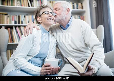 Senior uomo donna bacio sulla guancia con braccio intorno a lei. Foto Stock