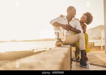 Bella gara nera africana di coppia in amore e vacanze sedersi godendo insieme con grandi sorrisi e ridere. abiti casual come stile di moda con Foto Stock