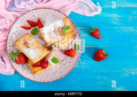 Gustosi dolci di pasta sfoglia dessert su piastra su sfondo di legno. Deliziosi biscotti fatti in casa con confettura di fragole, frutti di bosco e zucchero in polvere. Vista superiore Foto Stock