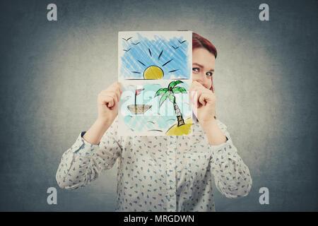 Felice imprenditrice nascondere faccia dietro un foglio di carta bianco con un posto esotico disegnato. Sognare di vacanza sul mare. Foto Stock