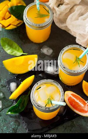 Rinfrescanti cocktail estivi fatti di agrumi e di mango, bevanda fredda o un drink con ghiaccio su una pietra scura sullo sfondo.