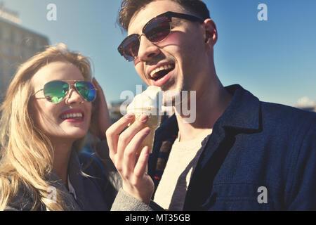 Felice caucasico romantico paio di occhiali da sole. Funny Girl mangiare il gelato Foto Stock