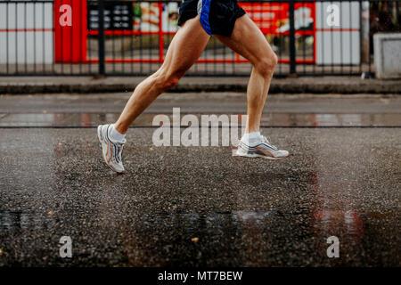 Piedi uomini runner in esecuzione su bagnato dalla pioggia asfalto grigio Foto Stock