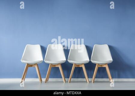 Vista frontale di una fila di moderni e sedie bianche e una rosa