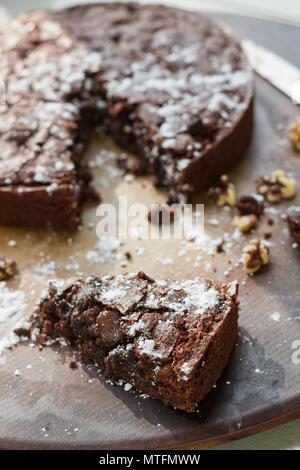 Brownie al cioccolato con zucchero a velo, le gocce di cioccolato e noci. Su una placca da forno. Foto Stock
