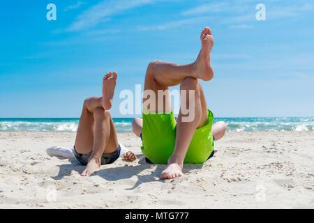 Padre e figlio avendo divertimento sulla spiaggia, posa su una spiaggia. Foto Stock