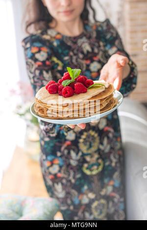 Foto di felice giovane donna in piedi in cucina nella cucina casalinga. Focus sulle frittelle. Foto Stock