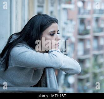 Bellissimo il latino premuto lonely donna a guardare fuori sensazione triste, dolore e preoccupazione su un balcone a casa. Crisi, depressione e salute mentale concetto
