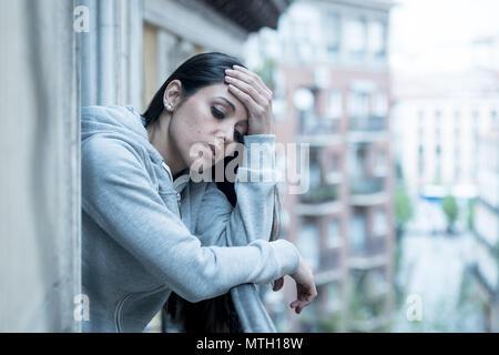 Bellissimo il latino premuto lonely donna a guardare fuori sensazione triste, dolore, dolore su un balcone a casa. Crisi, depressione e salute mentale concetto