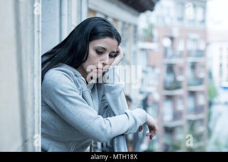 Attraente premuto latina lonely donna a guardare fuori sensazione triste, dolore, dolore su un balcone a casa. Crisi, depressione e salute mentale concetto