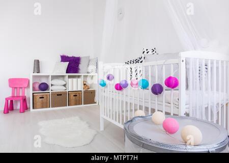 Un moderno design interno cameretta del bambino con culla bianco decorato con coloratissime palle. Sulla parete opposta ripiano con caselle e cuscini