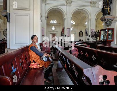 Galle, Sri Lanka - Set 9, 2015. Una giovane donna orante presso la chiesa a Galle, Sri Lanka. Galle è stato il porto principale dell'isola nel XVI secolo. Foto Stock