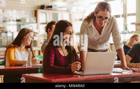 Ritratto di giovane insegnante aiutare uno studente durante le lezioni. Studente universitario di essere aiutato dal docente femmina durante la classe. Foto Stock
