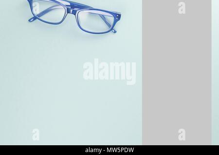 Coppia di cornice blu occhiali su una luce blu superficie - direttamente al di sopra di Foto Stock