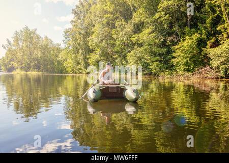 Pescatore con canne da pesca è la pesca in una barca in gomma sullo sfondo della splendida natura e lago o fiume. Campeggio turismo viaggio relax uno stile di vita attivo adventure concept Foto Stock