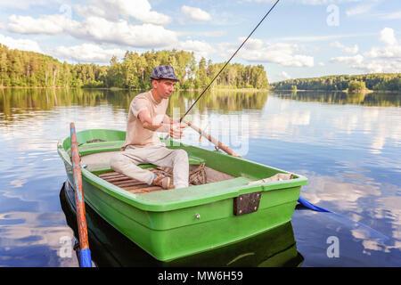 Pescatore con canne da pesca è la pesca in una barca di legno sullo sfondo della splendida natura e lago o fiume. Campeggio turismo viaggio relax uno stile di vita attivo adventure concept Foto Stock