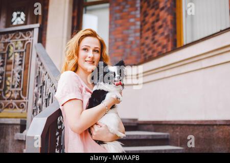 Una giovane e bella donna di colore rosso con capelli lunghi è in possesso di un piccolo simpatico divertente big-eyed cane di due fiori, una in bianco e nero il pet della razza di hichuahua Foto Stock