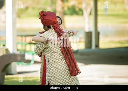 Indian lo sposo abbraccia la sposa nel parco Foto Stock