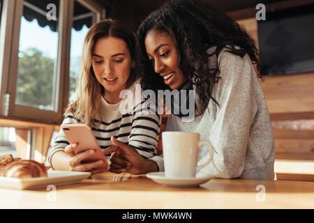 Due donne sedute in un ristorante guardando il telefono cellulare. Amici seduti in un caffè con caffè e snack sulla tabella guardando al telefono cellulare. Foto Stock