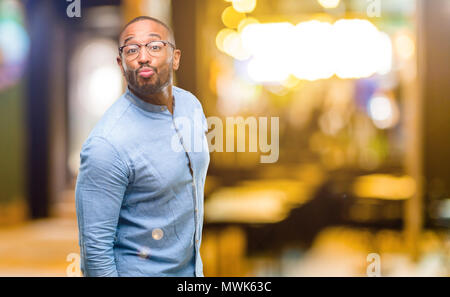 African American uomo con barba esprimere amore soffia kiss in telecamera, flirt di notte Foto Stock
