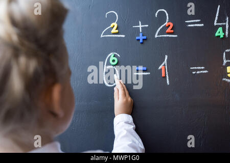 Ritagliato colpo di Little Schoolgirl Numeri di disegno sulla lavagna Foto Stock