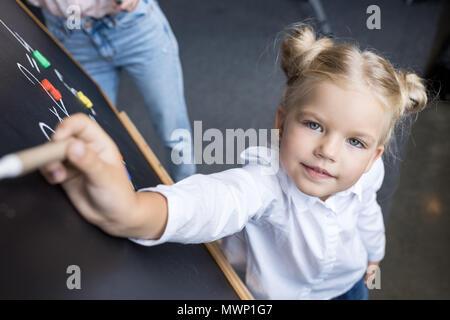 Adorable Little Schoolgirl Numeri di disegno sulla lavagna Foto Stock