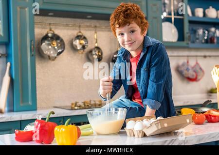 Carino Piccolo Ragazzo che sorride alla telecamera mentre la cottura in cucina Foto Stock