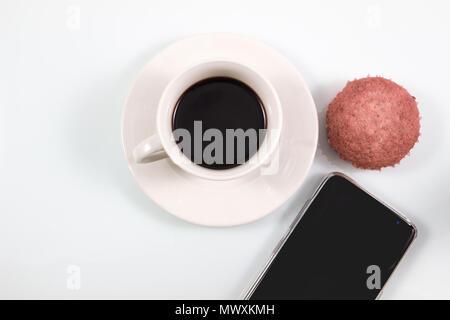 Vista superiore, caffè espresso in tazza bianca con fatti in casa muffin brownie torte e lo smartphone isolati su sfondo bianco, coffee break nel concetto di soft Foto Stock