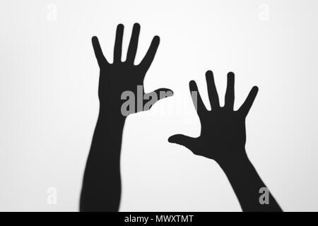 Ombre misteriose di mani umane su grigio Foto Stock