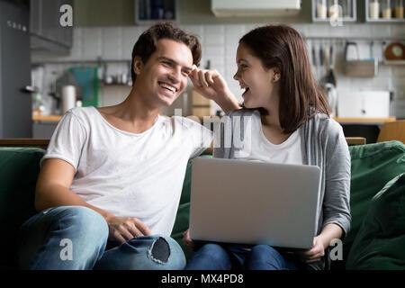 Felice coppia millenario ridere utilizzando laptop insieme su kitche Foto Stock