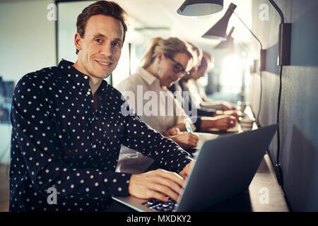 Sorridente giovani designer che lavora su un computer portatile mentre è seduto in una fila con i colleghi a una tabella in un ufficio moderno Foto Stock