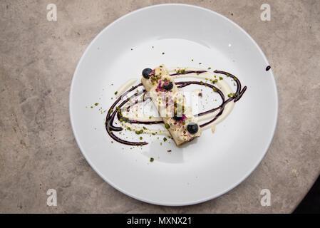 Buon cibo: una fetta di mirtillo Cheesecake con frutta fresca e una briciola di pistacchio Foto Stock