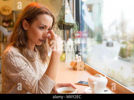 Giovane ragazza nel dolore di piangere dopo dissoluzione seduti con la tazza di tè al tavolo in una caffetteria vicino alla finestra Foto Stock