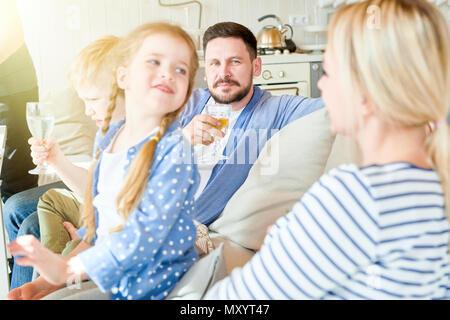 Ritratto di famiglia felice con due bambini seduti sul divano gustando una cena festosa parte a casa, focus sulla cute dai capelli rossi ragazza volgendo lo sguardo al suo mo Foto Stock